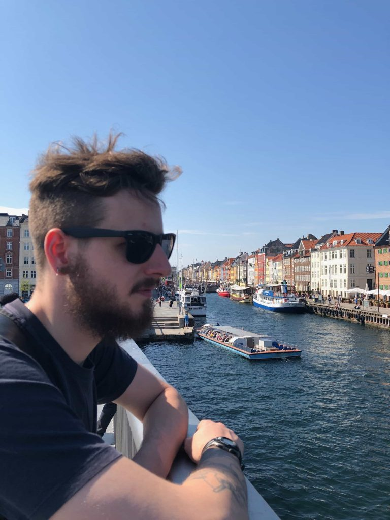 Boy in sunglasses standing by Nyhavn in Copenhagen