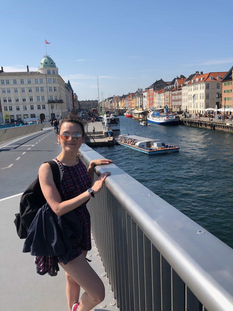girl standing on a bridge by Nyhavn in Summer in Copenhagen