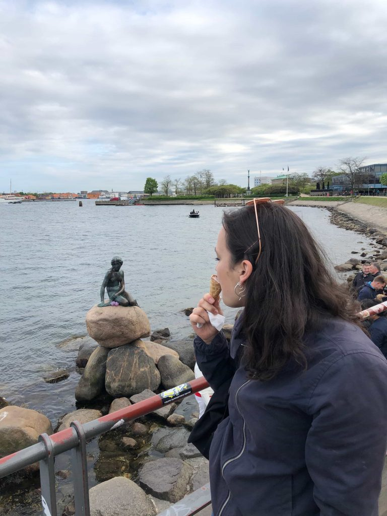 girl eating ice cream in front on the mermaid copenhagen