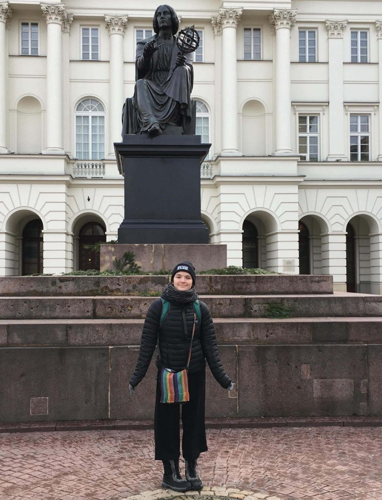 Girl standing in front of Statue of scientist, Nicholas Copernicus Warsaw Poland