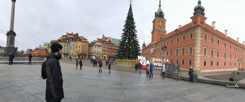 Man standing in Market Square Old Town in Warsaw Poland with a Christmas Tree.