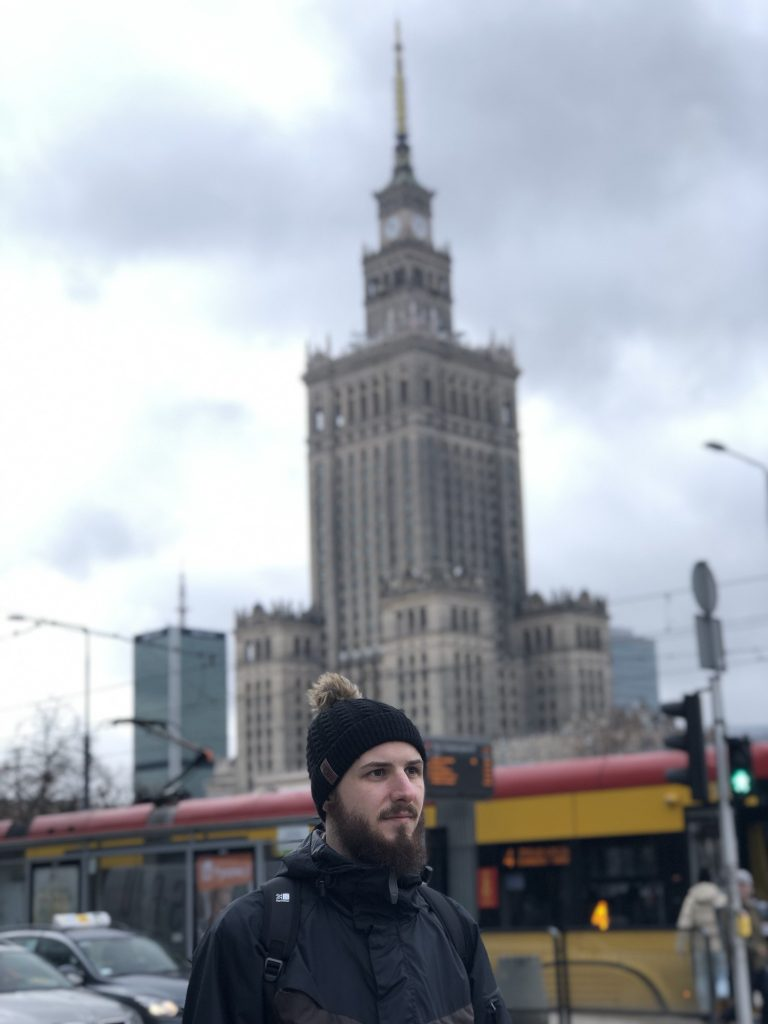 Man standing in front of The Palace of Culture & Science - aka Stalins Penis. Warsaw Poland