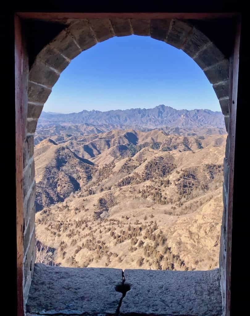 view of the mountains through an arch on the great wall of china