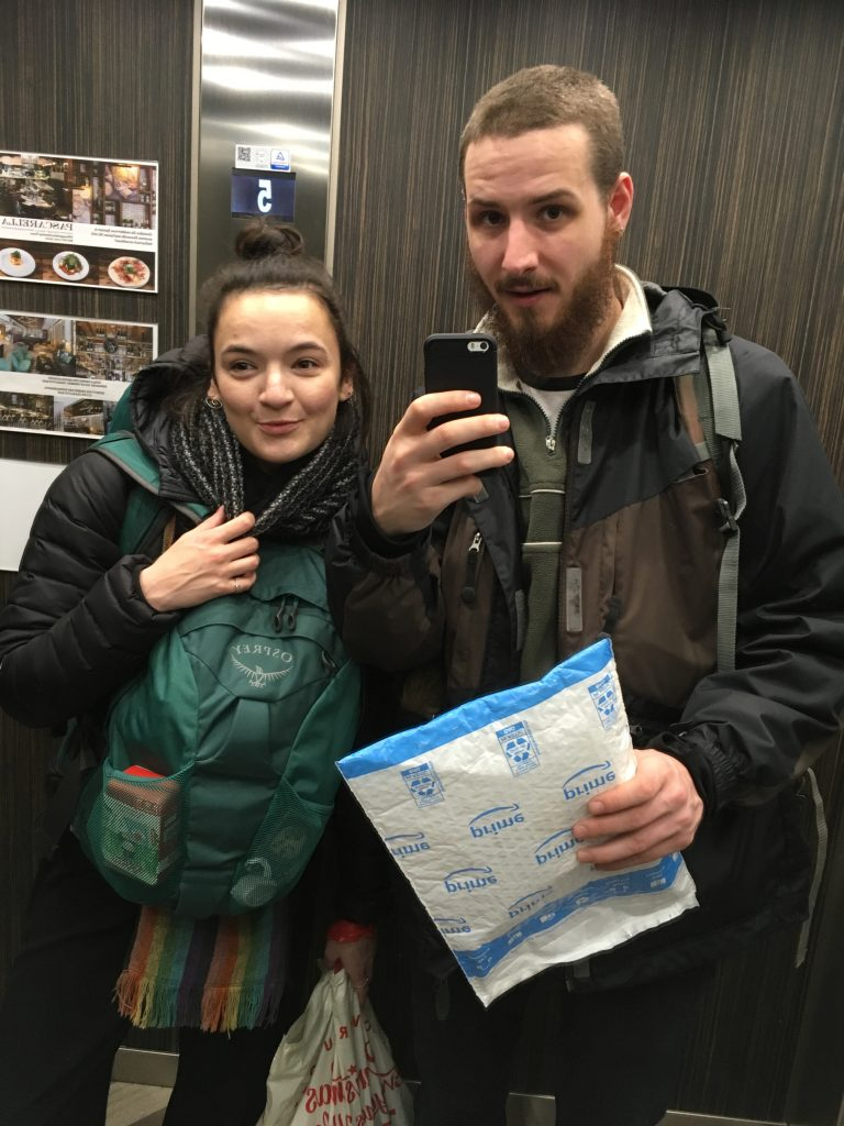 Boy and a Girl in a lift with traveller backpacks on