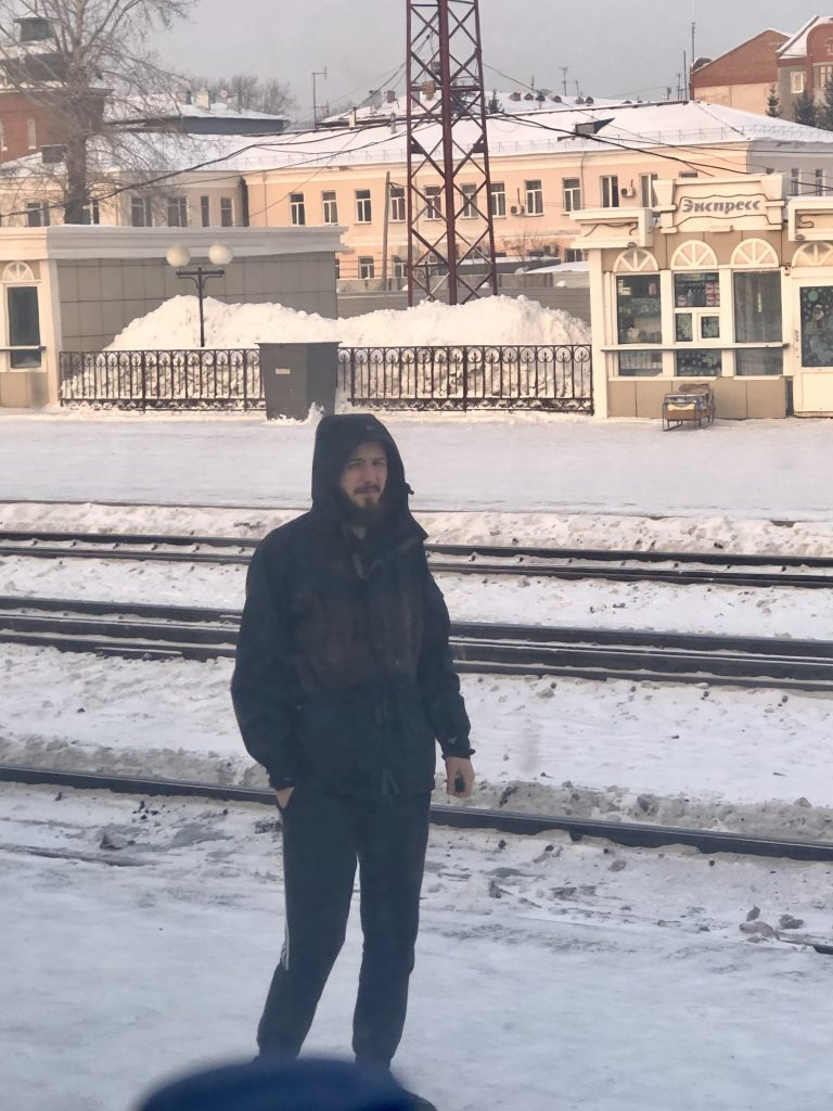 Picture taken from inside a train of a Boy standing outside smoking on the snowy platform in Siberia as he waits for the train to leave.  Exactly What to Expect from the Trans Siberian Railway www.thedancingcircustraveller.com